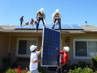 Workers install solar panels on the house of a low-income family in Los Alamos, California.