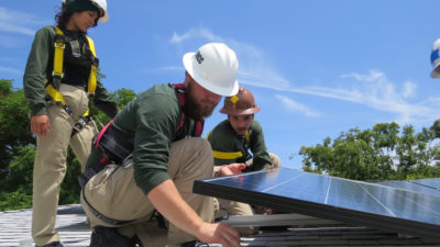 Workers install a solar electric system on the Sacramento home of a disabled man who lives on a fixed income. The system will provide an estimated $22,800 in energy savings over its lifetime.