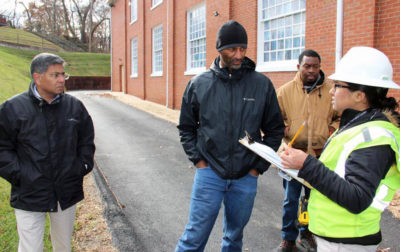 Solar contractor Brad Boston (center) and utility representatives meet with engineer Pranay Kohli to discuss a community solar project at DuPont Park Seventh Day Adventist Church in Washington, D.C.