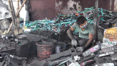 A worker dismantles toner cartridges in Guiyu, China.
