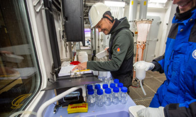 Oceanographer Colin Stedmon prepares water samples for acidification measurements aboard the Kronprins Haakon.