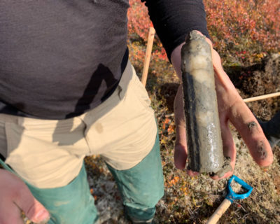 Researchers Evan Wilcox [left] and Niels Weiss extract ice-rich permafrost cores [as seen in photo, right] from the tundra.