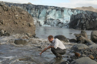 Biogeochemist Peter Wynn of Lancaster University collects a sample of meltwater from the Sólheimajökull glacier in Iceland.