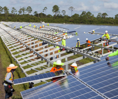 Workers install panels last year at the Babcock Solar Energy project in Punta Gorda, Florida. The project is one of eight new utility-scale solar farms in the state set to be completed by early 2018.