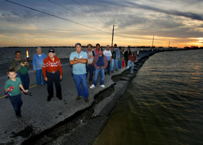 Chief Albert Naquin (with arms folded) and members of his tribe of Biloxi-Chitimacha Choctaw Indians on the Isle de Jean Charles lake road, which has eroded to one lane, in November 2008.