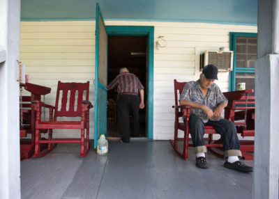 "Isle de Jean Charles resident Wenceslaus Billiot (in doorway) and his wife host friends each afternoon at 3 p.m. for tea, where they sit and talk about the day. ""In another 20 years there will be probably a couple feet of water around here,"" he said."