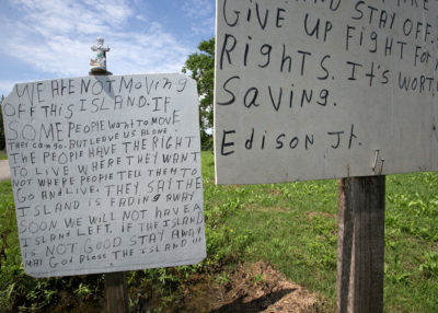 A sign on the island road, erected by Edison Dardar Jr., reflects the opposition of some residents to the proposed move to higher ground.