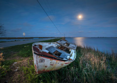 An abandoned boat lays washed up on the island road, with the lights of Point Aux Chene on the horizon. The road that links the islanders to nearby towns now floods regularly.