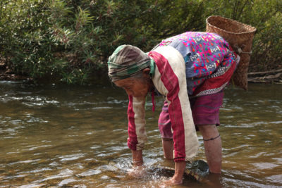 A Karen woman captures fish with a traditional net in the park.