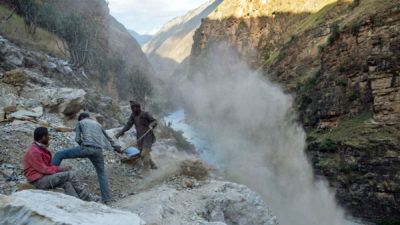 Villagers work to clear terrain for a new road along the Karnali River below the Nepalese village of Tamcha in September 2018.