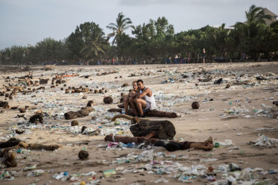 Vacationers sit amid scattered plastic waste on Kuta Beach, one of Bali's top tourist destinations.