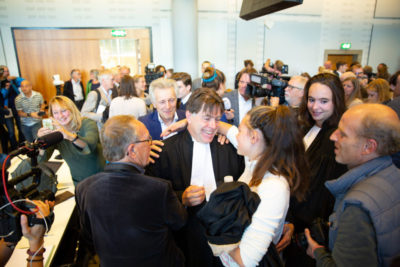 Lawyers and plaintiffs celebrate on October 9 after The Hague Court of Appeal upheld a ruling that the Dutch government must stick to its commitment to cut greenhouse gas emissions by 25 percent within five years.