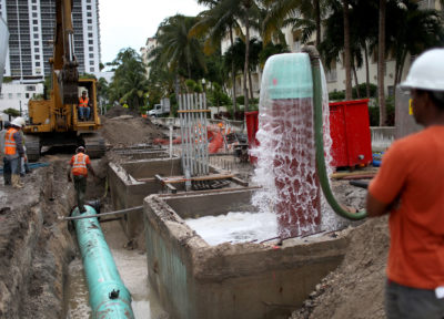 Workers install a water pump system to combat rising sea levels in Miami Beach.