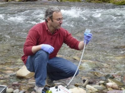 U.S. Forest Service biologist Michael Schwartz gathers water to be sampled for eDNA from Rattlesnake Creek in Montana.