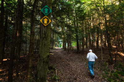Earle Peterson walks through his 1,200-acre property in Burlington, New York, which is protected through a conservation easement.