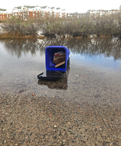 An overturned trash can sits in high-tide floodwaters on 52nd Street in Norfolk, Virginia.