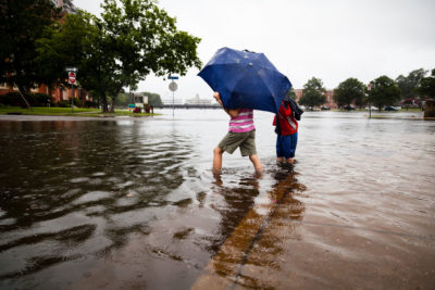 Children play in flooded streets in front of the Chrysler Museum of Art in Norfolk, Va.
