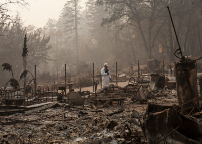 A member of the California Army National Guard walks through the burnt remains of a house in Paradise, California following the deadly Camp Fire in November 2018.