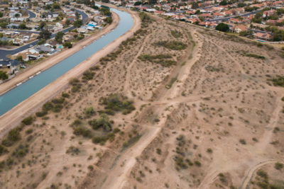 The remnants of canals used by the Hohokam people for centuries can still be seen in the sandy soil here in Mesa, Arizona, with the ancient canal path running parallel to the modern-day South Canal, which carries water from the Salt River.