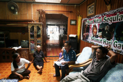 Environmentalist Jok Jau Evong (far right) and headman Gasah Anak Tadong (right, in chair) meet with community members in the Sungai Buri longhouse.