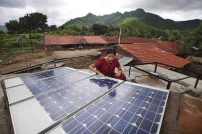 A woman inspects solar panels in the rural village of Tinginaput, India.
