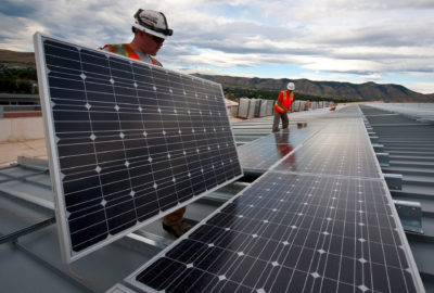 Workers install solar panels as part of a U.S. Department of Energy/Xcel project in Colorado.