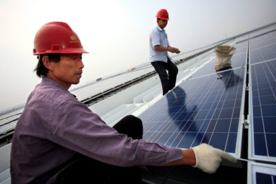 Workers install solar panels on the roof of the Hongqiao Passenger Rail Terminal in Shanghai, China.