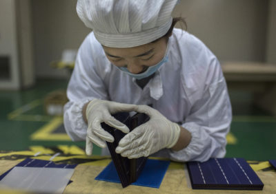 A technician inspects a solar cell on the production line at Yingli Solar in Hebei Province, China.