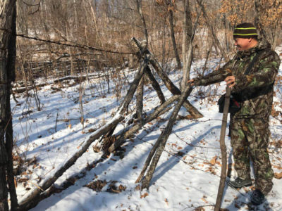 Li Dongwei of the Chinese forest service stands by a fence that currently separates tiger and leopard habitat from nearby farms.