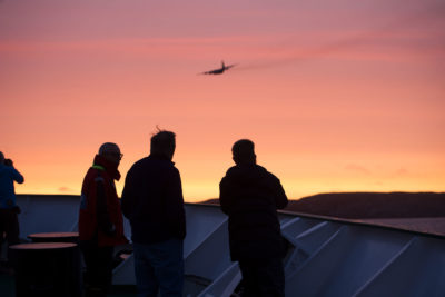 Passengers aboard the Akademik Ioffe watch as a plane arrives from the Canadian National Defence Joint Rescue Coordination Centre in Ontario. It took nine hours for the plane to get to the grounded vessel.