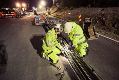Workers install Sweden's electric road, located outside Stockholm.