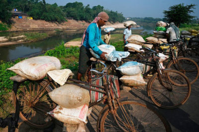 Workers load their bicycles with sacks filled with sand from the Kangsabati River to be used in construction in towns near Kolkata.