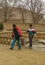Children in rural Gansu province collect water from a well on the grounds of their school.